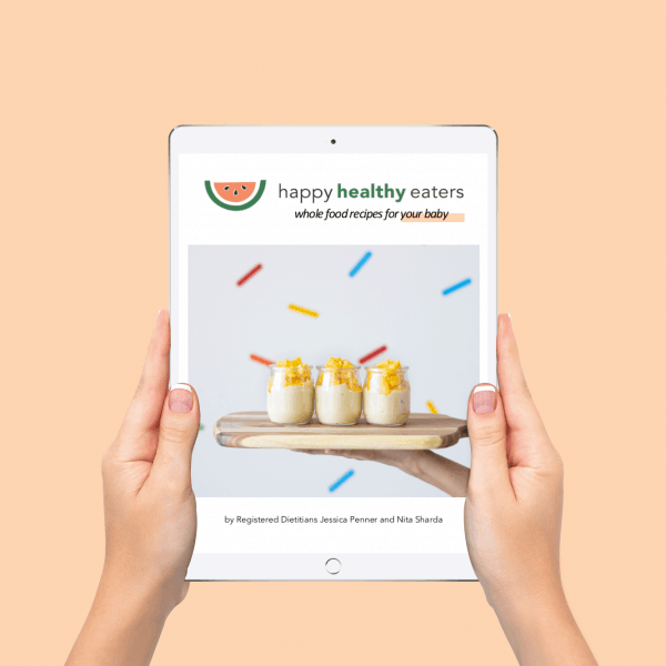 hands holding iPad with cover of whole food recipes for your baby on a peach background