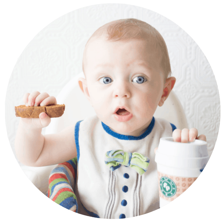 Baby holding pumpkin spice biscotti with Fisher Price Coffee Cup teething toy