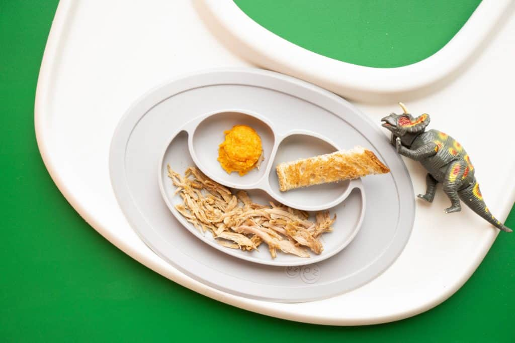 Baby plate with shredded chicken, toast strip, and sweet potato puree.