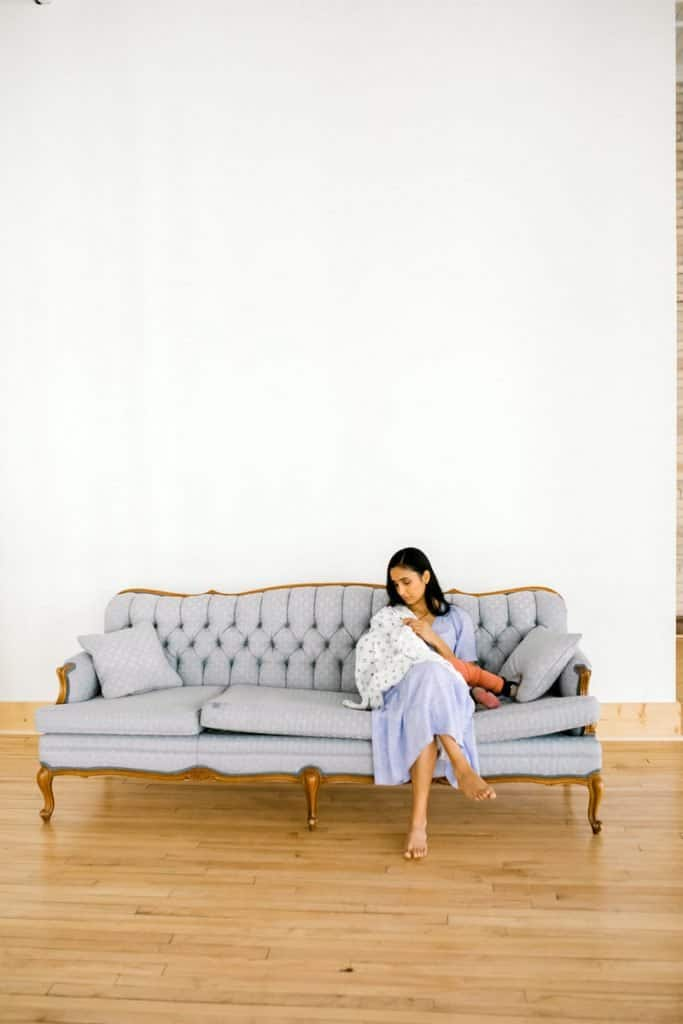 Mother with long black hair nurses baby under a blanket on a couch in front of a white wall.