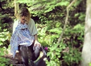 Mother breastfeeding baby under a nursing cover in the woods