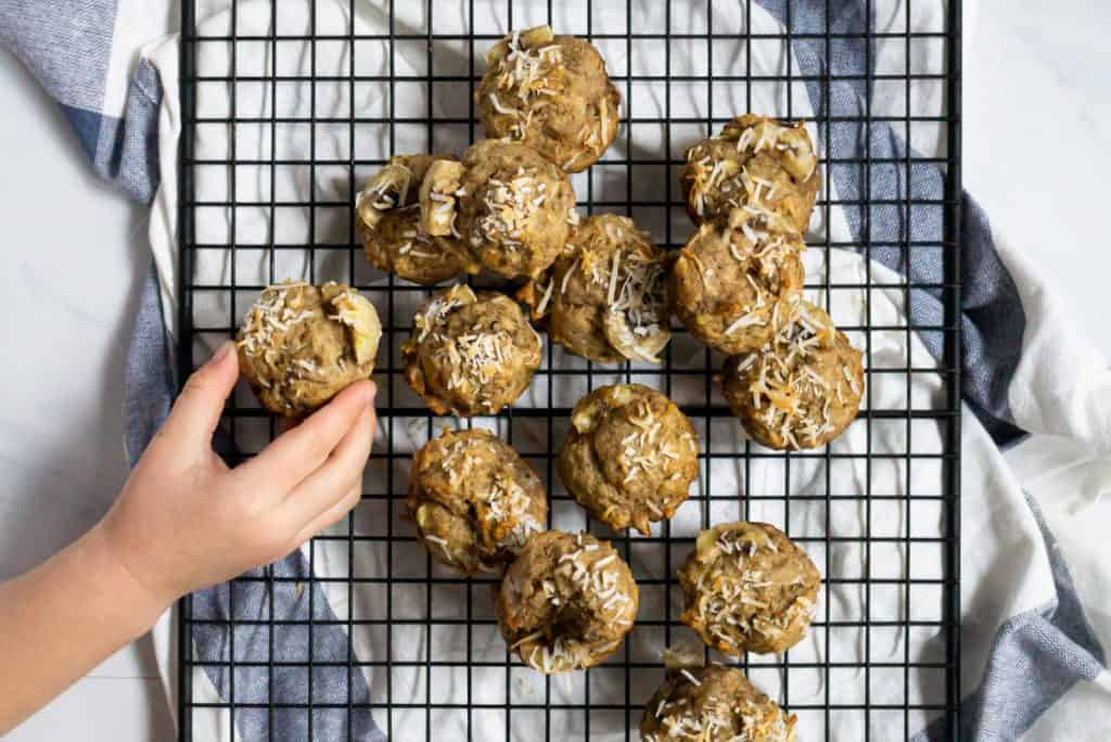 Mini coconut baby banana muffins on a cooling rack with a toddler hand reaching to grab one muffin.