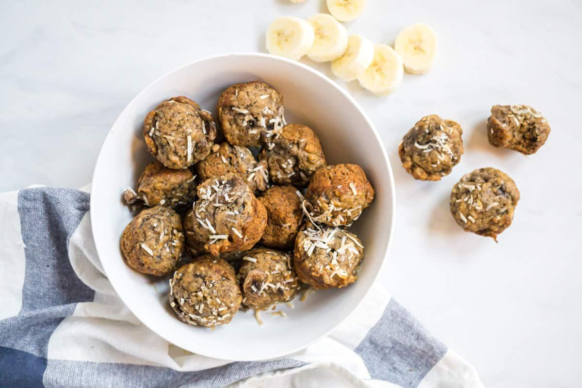 a white bowl of mini coconut banana baby muffins