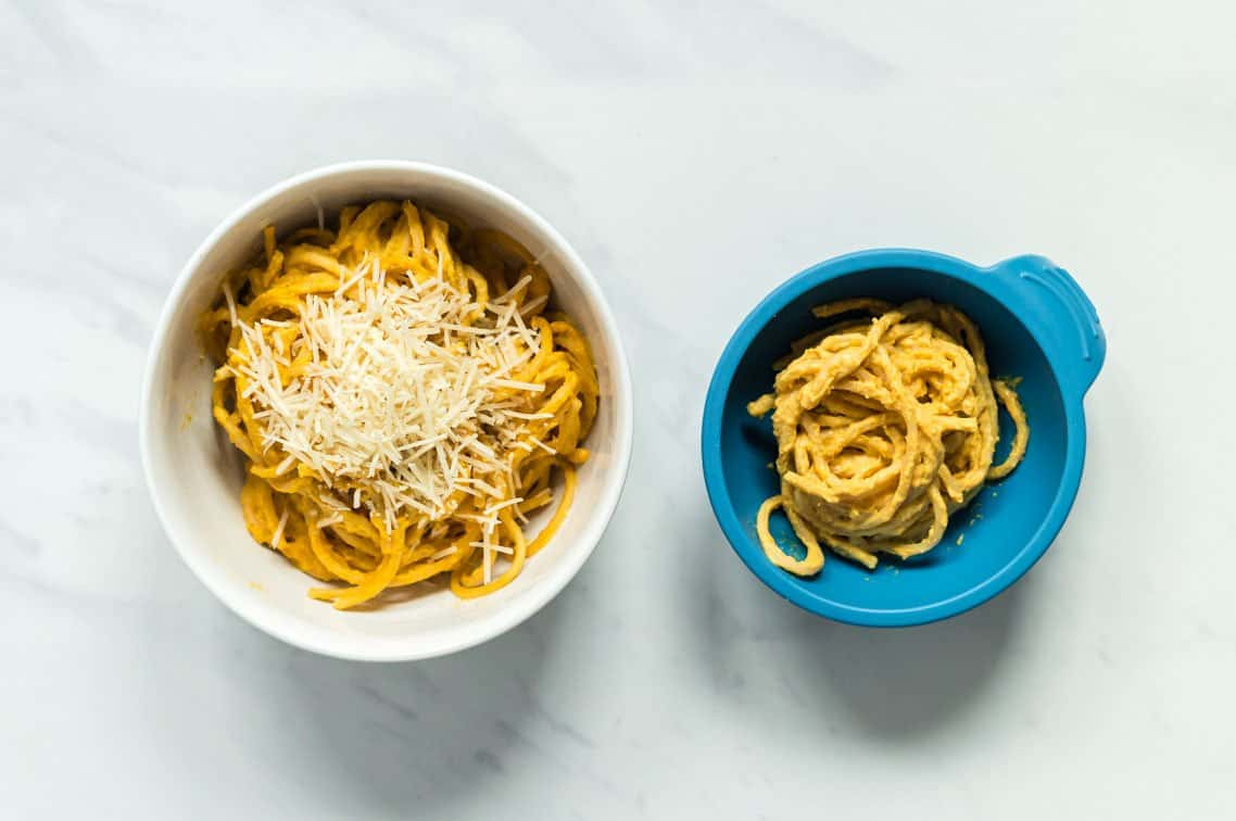 A side by side image of a bowl of creamy pumpkin spaghetti for the family and a bowl with slight adaptations for baby