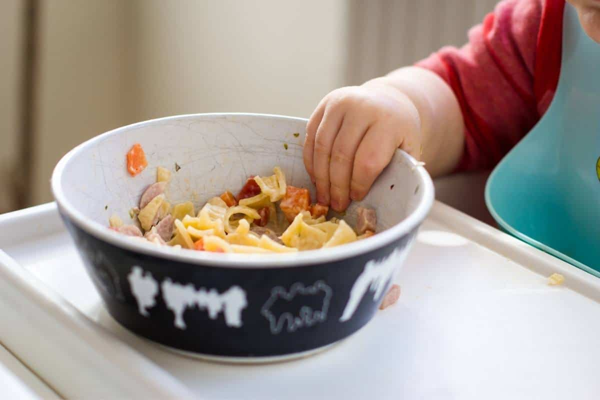 A bowl of noodle soup on a tray with a baby reaching for it
